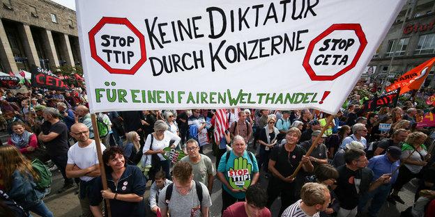 ARCHIV - Teilnehmer der Ceta und TTIP Demonstration halten am 17.09.2016 auf dem Arnulf-Klett-Platz in Stuttgart (Baden-Württemberg) ein Transparent mit der Aufschrift «KEINE DIKTATUR DURCH KONZERNE». Sie demonstriert gegen die Freihandelsabkommen Ceta und TTIP. (zu dpa Jahresrückblick vom 16.12.2016) Foto: Silas Stein/dpa +++(c) dpa - Bildfunk+++