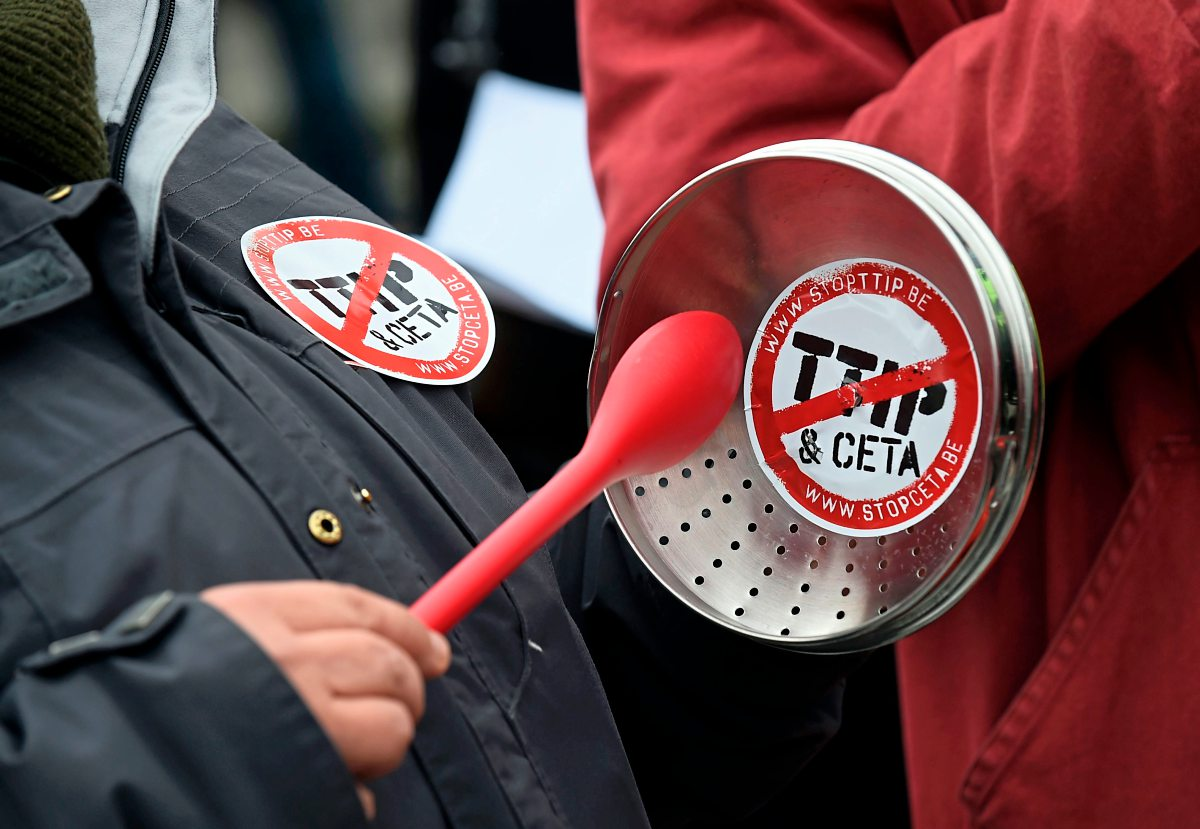 "A demonstrator holds a lid with a sticker reading ""TTIP & CETA"" crossed during a protest against the EU-Canada Comprehensive Economic and Trade Agreement (CETA) at European Union Commission headquarters in Brussels on October 27, 2016. Belgium announced on October 27, 2016 a breakthrough in talks to secure a landmark EU-Canada trade deal by winning over the leaders of a recalcitrant Belgian region, potentially snapping a deadlock which threatened European credibility anew. However, the announcement came too late for EU leaders and Canadian Prime Minister Justin Trudeau to go ahead with a signing ceremony in Brussels on October 27, 2016.  / AFP PHOTO / JOHN THYS"